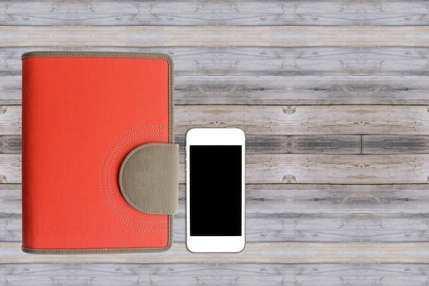 木製のテーブルの上にスマートフォン