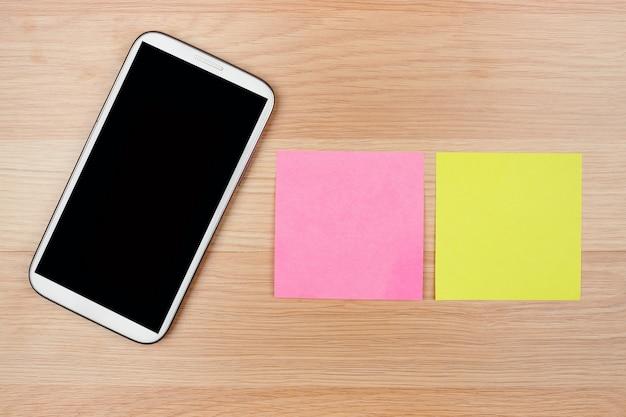 木製の背景、ビジネスコンセプトに空の空白のメモと木製のプレート上のスマートフォン