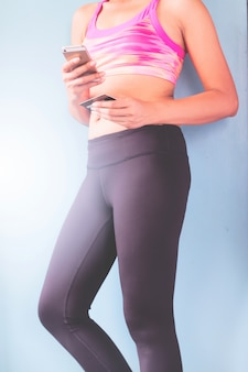 Smart phone online shopping in woman hand.  fitness clothing at sport club background. buy sport items with e commerce web site