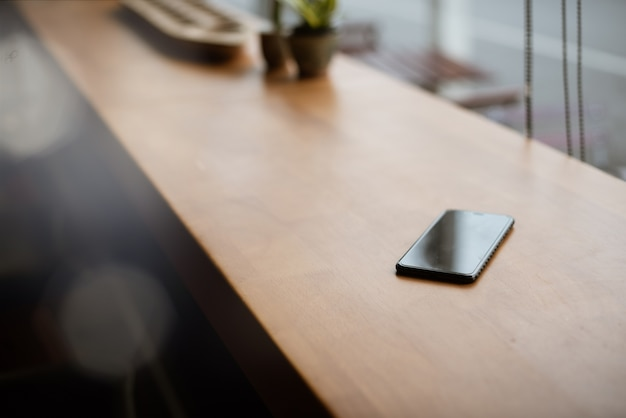 Smart phone place on wooden table in coffee shop
