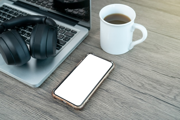 Smart phone white mock up screen. working place office desk. flat lay workspace with laptop cup of coffee on wooden background.