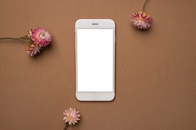 Smart phone with blank screen in frame of dried flowers on brown surface