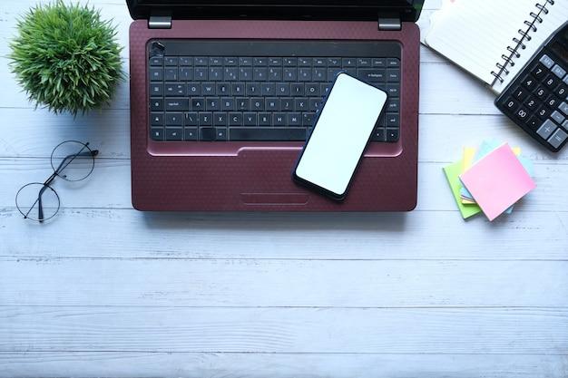 나무 배경에 빈 화면 노트북이 있는 스마트 폰