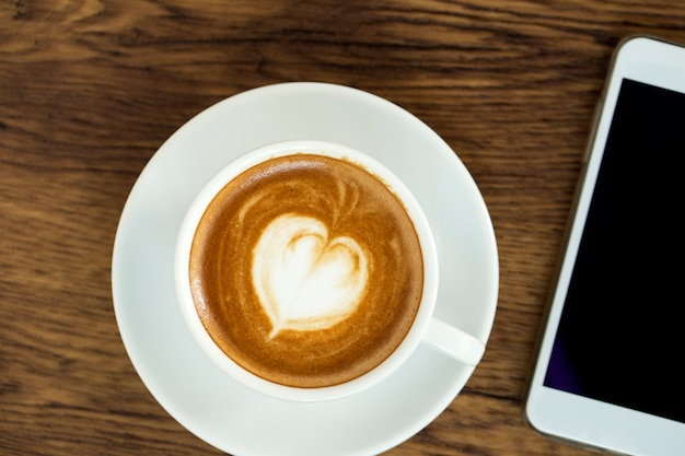 Smart phone with latte art coffee on wooden background