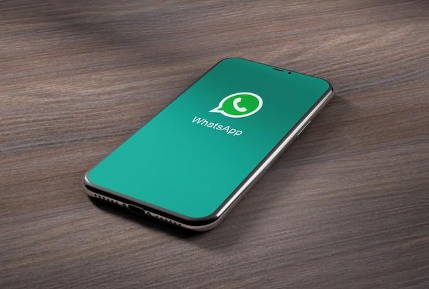 나무 테이블에 whatsapp 응용 프로그램이있는 스마트 폰