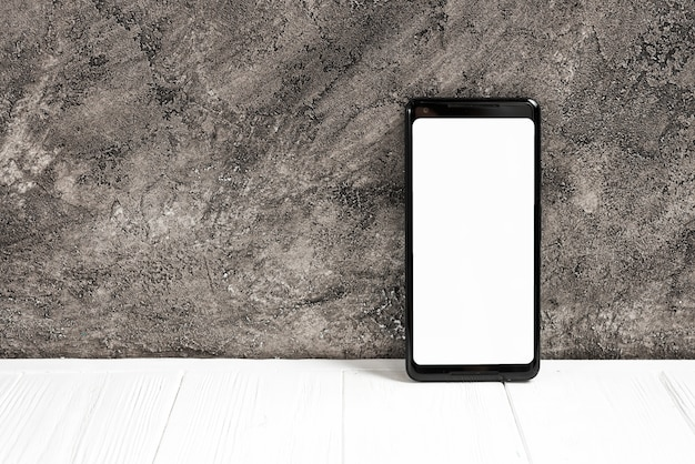 Smart phone with white display screen on white table against concrete wall