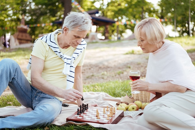 Умная позитивная старшая пара, выражающая миролюбие, играя в шахматы и отдыхая на открытом воздухе