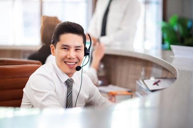 스마트 전문 아시아 남자 운영자, 콜 센터 부서에서 얼굴을 웃 고. 행복한 서비스 마인드 통신 부서와 협력