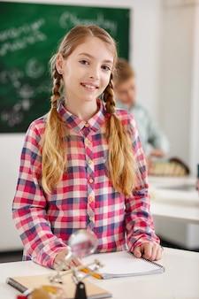 똑똑한 눈동자. 쓸 준비가되어있는 동안 당신에게 웃고있는 긍정적 인 지적인 소녀