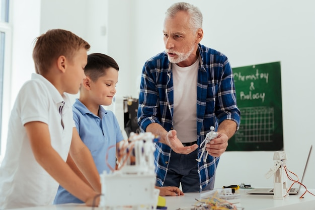 Smart pupils. nice pleasant man holding a robot model while talking to his pupils