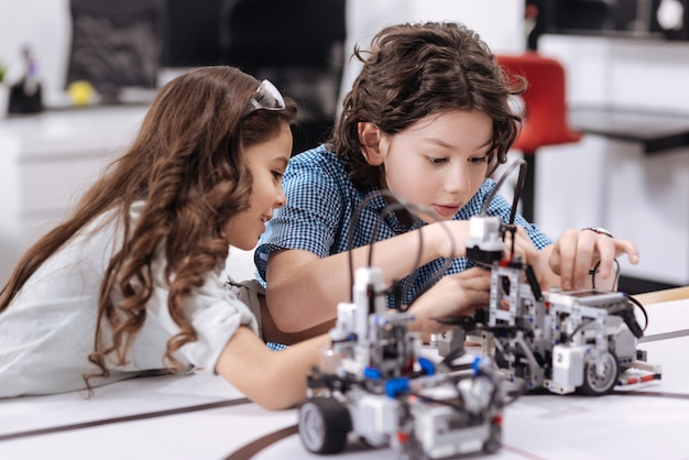 Smart pupils working . positive happy smart pupils sitting at class and repairing robot while working on the project