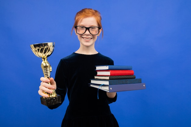 Smart red-haired teenager girl in glasses with a stack of books and a victory cup on a blue studio background.