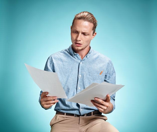 Умный грустный студент с листами бумаги