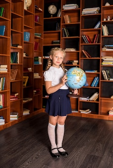 Smart school girl in uniform stands with a globe in the school library