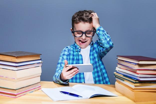 スマートpcはタブレットpcで宿題をしています。教室で彼の電話で遊んでメガネの若い生徒。