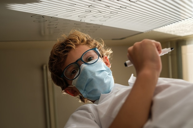 Smart schoolboy in mask in classroom during lesson