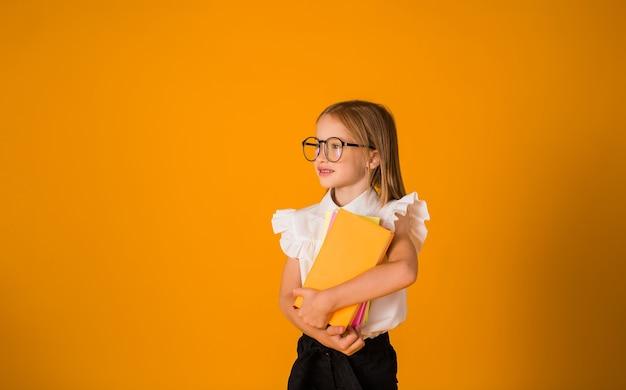 안경을 쓴 제복을 입은 똑똑한 여학생은 노란색 배경에 책이 있는 공간 사본을 들고 있다