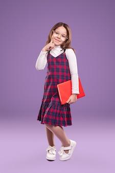 Умная школьница в униформе и очках с книгой
