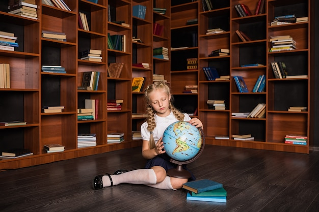 Smart schoolgirl studies the globe in the library