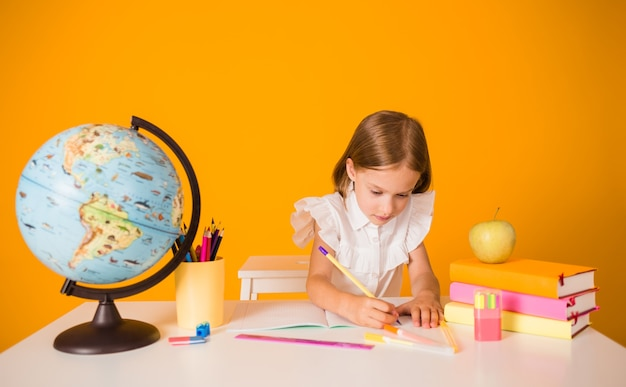 Smart schoolgirl in a uniform is sitting at a table with school supplies and writing in a notebook on a yellow background with a place for text