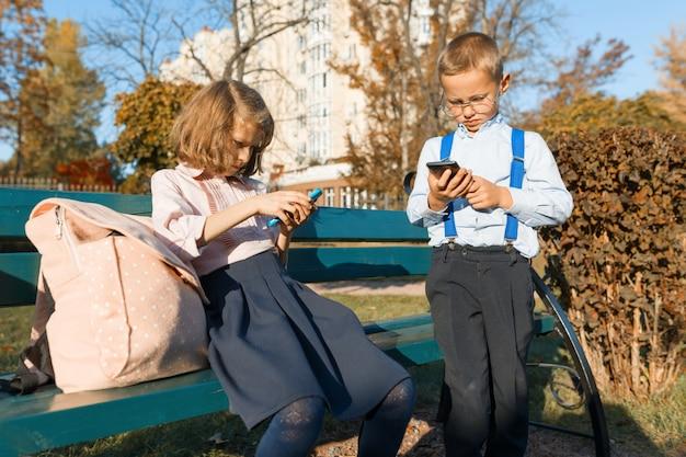 スマートな真剣な子供たちの男の子と女の子は、スマートフォンを探しています。