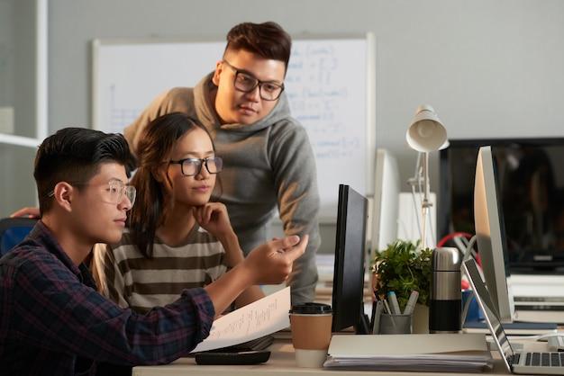 スマートで真面目なコンピュータサイエンスの大学生がコンピュータ画面に集まり、ソフトウェアのアーチについて話し合った...
