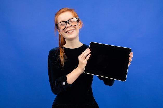 眼鏡をかけたスマートで真面目な赤毛のティーンエイジャーの女の子は、青い背景にページを挿入するために、空白の画面のモックアップでタブレットを保持しています。