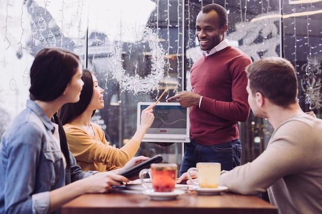똑똑하고 능숙한 4 명의 동료가 아이디어를 제안하고 웃으면 서 토론