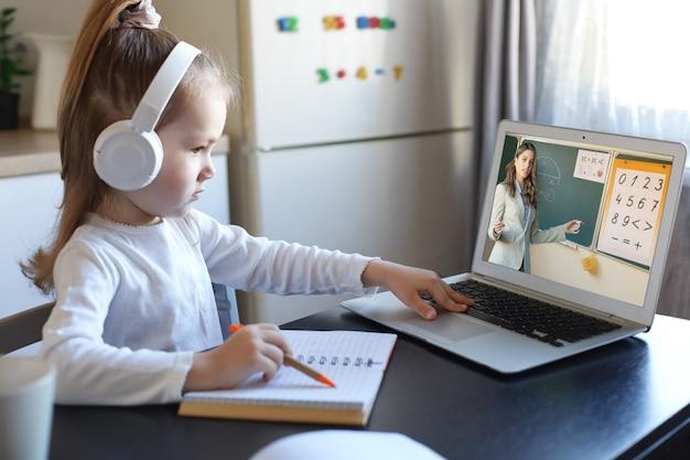 ヘッドホンをつけたスマートな小さな未就学児の女の子がオンラインレッスンを見て、自宅の先生とコミュニケーションを取ります。イヤホンをつけた小さな子供は、ラップトップのワイヤレス接続を使用してインターネットで勉強します。