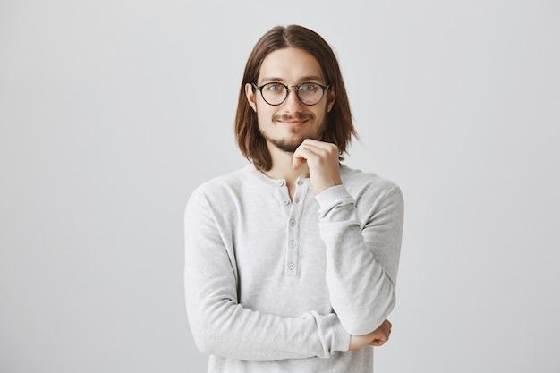 Умный улыбающийся человек в очках с интересом слушает