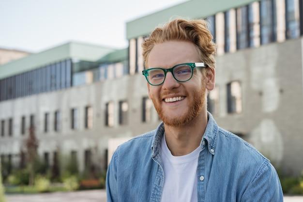 大学のキャンパスに立っているカメラを見ているスマートな笑顔の学生