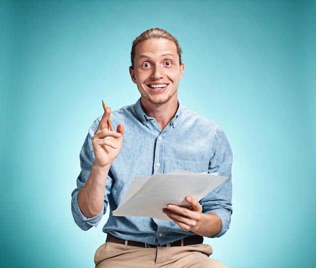 Умный улыбающийся студент с отличной идеей держит листы бумаги