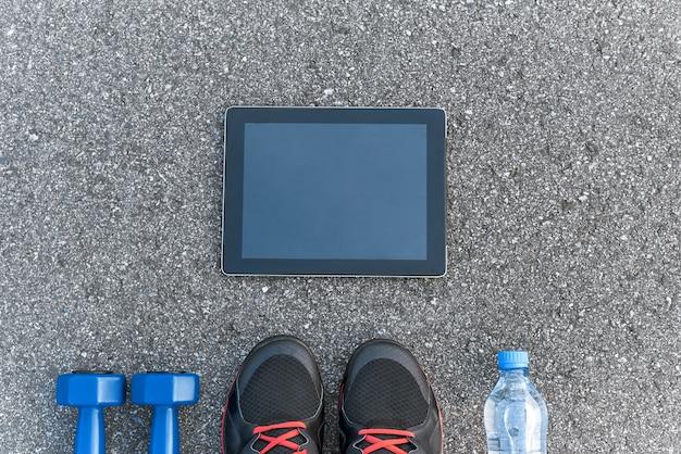 スマートスポーツガジェット。アスファルトの背景にあるダンプベル、水、黒のスニーカーのトリミングされた写真。スポーツモチベーションモバイルアプリ