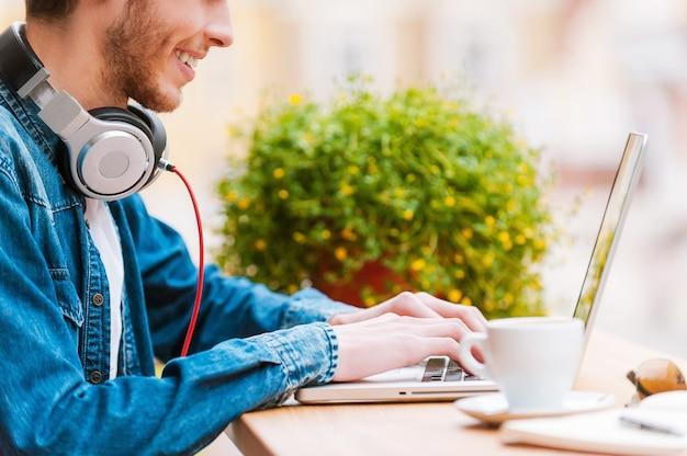 完璧なスタイルのためのスマートテクノロジー。ノートパソコンで作業している笑顔の若い男のトリミング画像