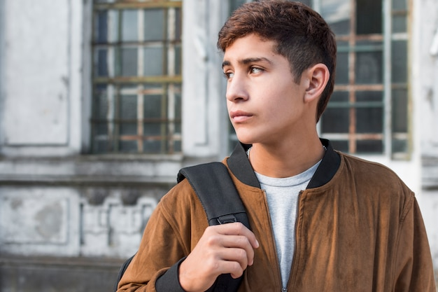 Smart teenage boy carrying backpack looking away
