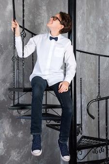 Шикарный подросток в очках сидит на винтовой лестнице в квартире-лофте девочка-подросток в белом ...