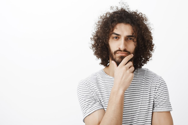 Smart thoughtful attractive hispanic guy with beard and curly hair, holding hand on chin, thinking