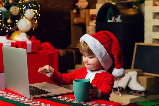 Умный интернет-серфинг для малышей. маленькая шляпа и костюм санта мальчика. мальчик ребенок с ноутбуком возле елки. покупайте рождественские подарки онлайн. рождественские покупки концепции. служба подарков. маленький помощник санты.