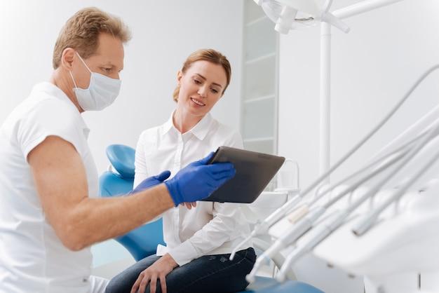 Умный обученный местный врач использует свой планшет, чтобы показать пациенту некоторые моменты, которые он хочет обсудить с ней перед лечением