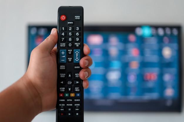 Умный телевизор и ручной пульт дистанционного управления. рука держит пульт от телевизора с телевизором в фоновом режиме. закройте вверх.