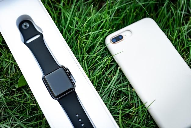 Умные часы и мобильный телефон на фоне травы.