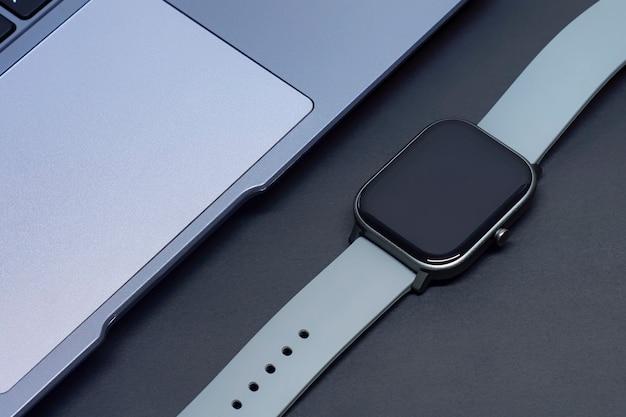 Умные часы и серебряный ноутбук на темном фоне.