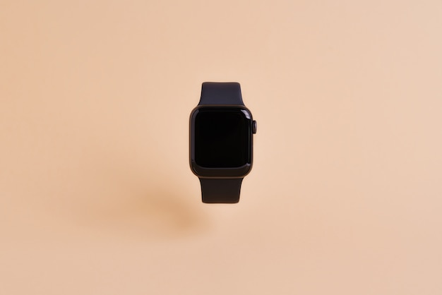Smart watch device isolated on light orange wall