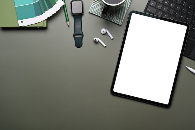 Smart watch, digital tablet , wireless keyboard and color swatches on dark green table.
