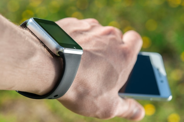 Smart watch on the hand that holds the phone.
