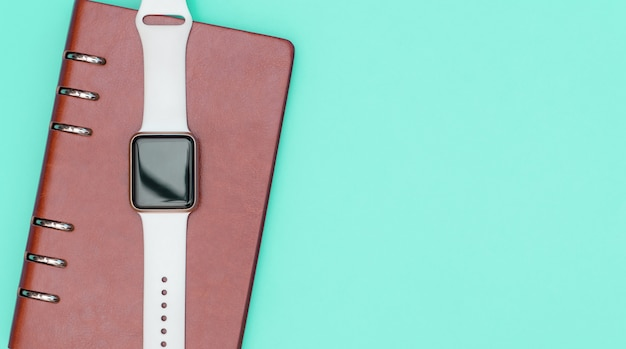 Smart watch on notebook for organize concept with teal copy space