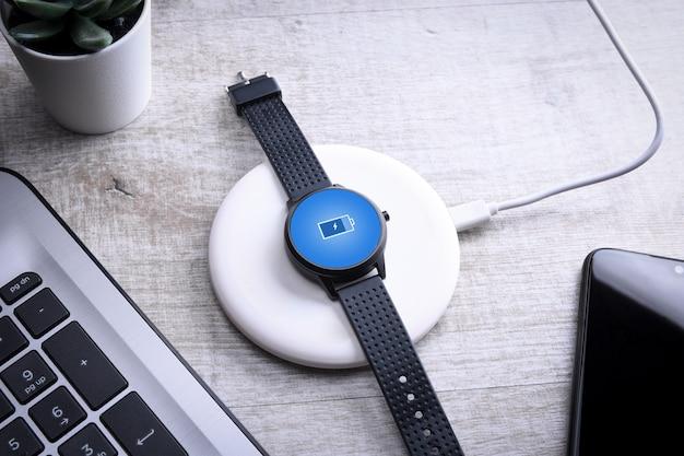 화면 충전 표시기가있는 무선 충전의 스마트 시계. 데스크탑 근처, 노트북 근처. 평면도. 텍스트를위한 장소