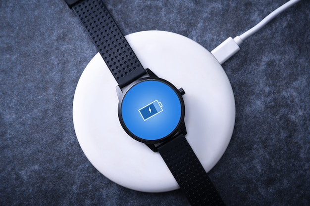 화면 충전 표시기가있는 무선 충전의 스마트 시계. 데스크탑 근처, 노트북 근처. 평면도.