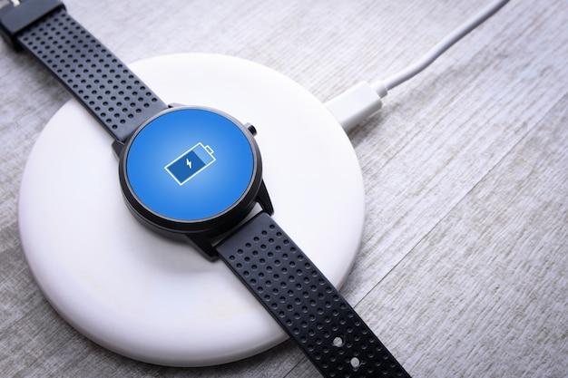 画面上の充電インジケータ付きのワイヤレス充電のスマートウォッチ。デスクトップ、ラップトップの近く。上面図。