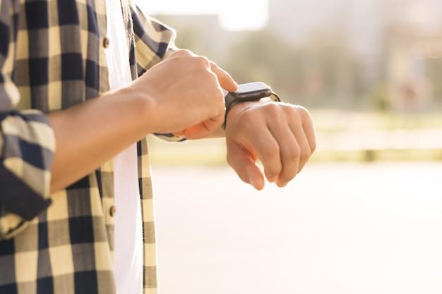 スマートウォッチスマートウォッチ男性の手にスマートウォッチ屋外の男性の手がスマートウォッチに触れる